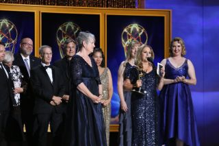 People pose as they receive an award in long formal sparkly dresses and suits