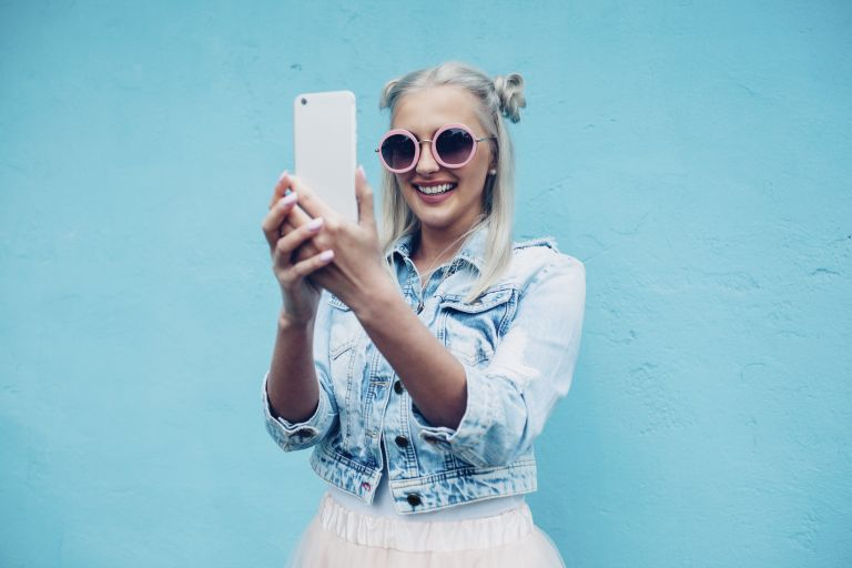 Happy fashionable young woman talking selfie against blue wall
