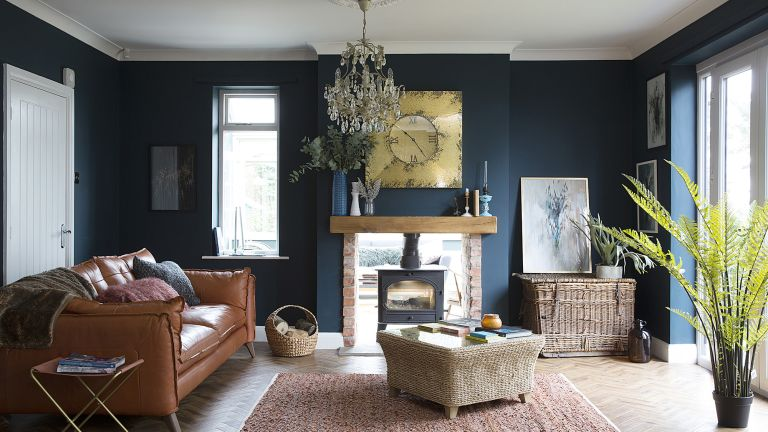 Living room with dark blue painted walls and a feature fireplace with woodburning stove