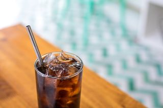 A reusable metal straw in a glass.