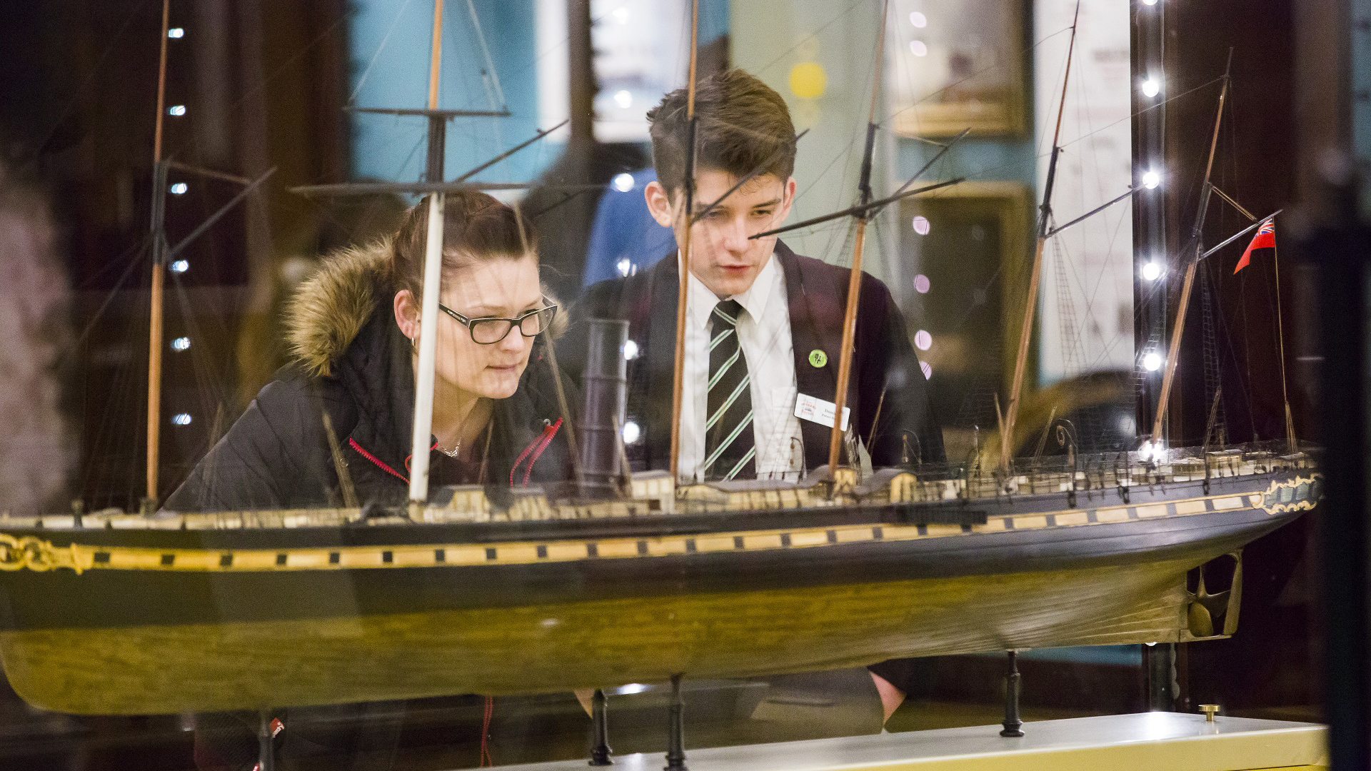 visitors looking at a model of the SS Great Britain