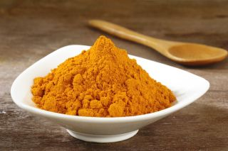 Turmeric powder sits in a bowl