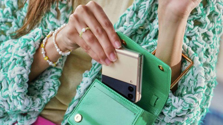 Samsung Galaxy Z Flip 3 5G handset shown being placed into a woman's handbag