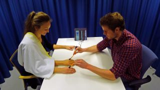Study researcher Arvid Guterstam creating the third arm illusion on a participant.