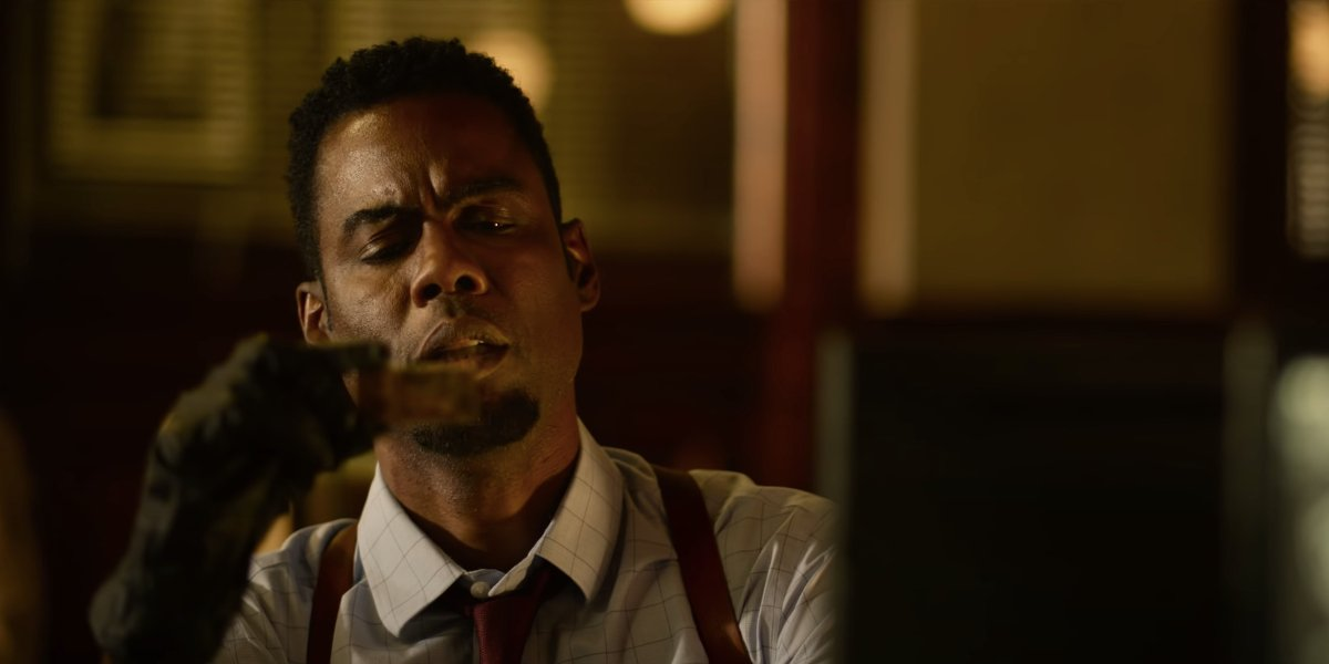 Chris Rock puzzles over a flash drive in his hands in Spiral: From the Book of Saw.