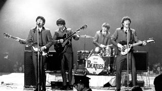 The Beatles perform onstage at the Washington Coliseum on February 11, 1964 in Washington, D.C.