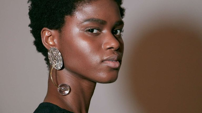 A model backstage with glowing skin to depict the debate for how to use foundation and BB cream together