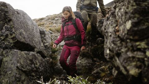 A women descends a rocky slope in Fjallraven Keb trousers