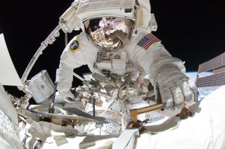 NASA astronaut Greg Chamitoff takes center stage in this amazing spacewalk photo taken by crewmate Mike Fincke (visible in the reflection on Chamitoff's spacesuit visor) using a fish-eye lens and digital camera during a May 27, 2011 excursion outside the