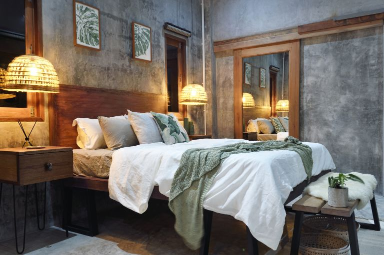 Hotel bedroom with concrete furniture and white bed linen