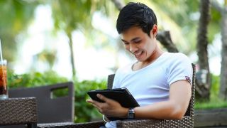 Man with an android tablet outdoors, using the best PDF reader for Android.