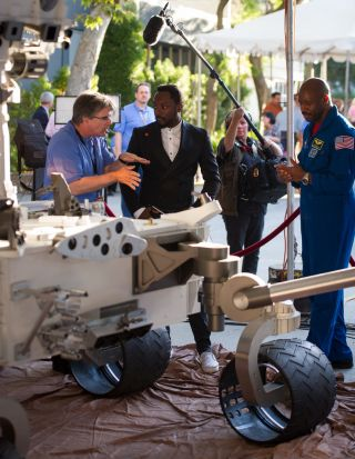 Musician Will.i.am, center, listens to NASA scientist Jim Garvin of the Goddard Space Flight Center talk next to a mock up of the Mars Science Laboratory rover Curiosity.