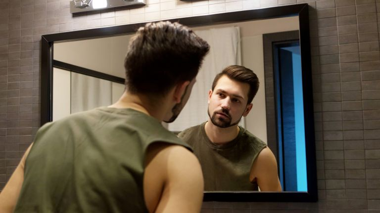 Man looking in mirror body image