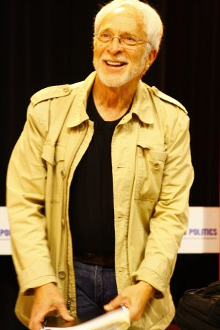 Author Lee Gutkind wearing a tan coat, black shirt and blue jeans.