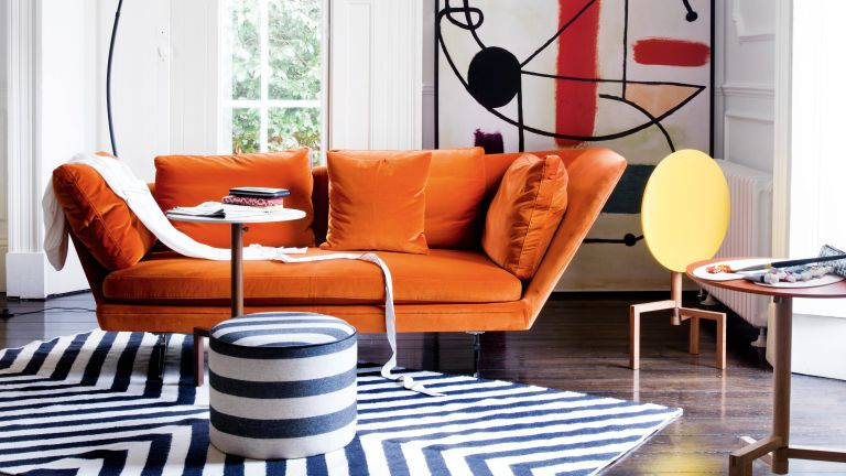 Modern living room with orange sofa, striped rugs and artwork