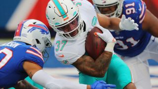 Myles Gaskin #37 of the Miami Dolphins is tackled by Dane Jackson #30 of the Buffalo Bills at Bills Stadium on Jan. 3, 2021 in Orchard Park, New York.