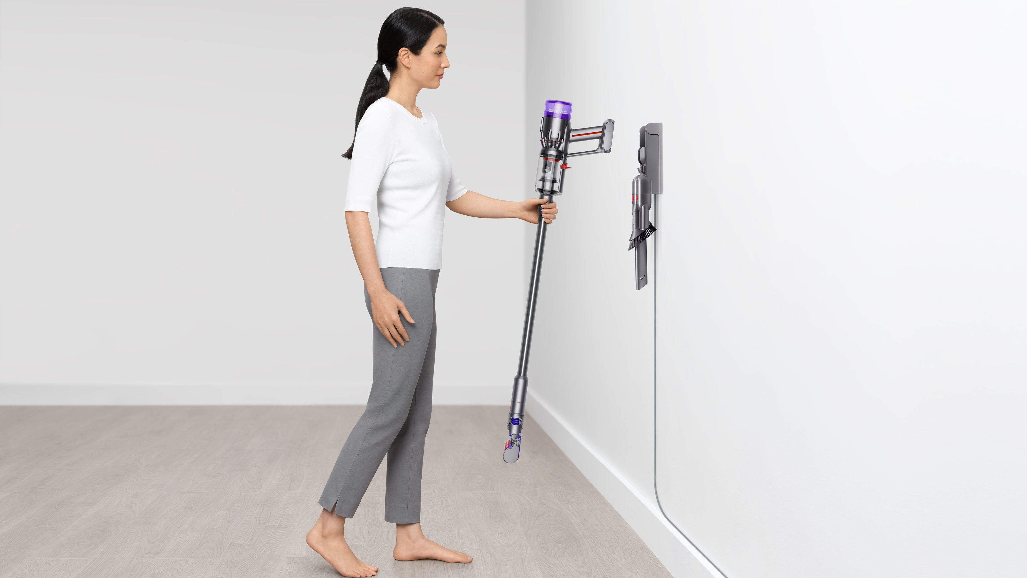Dyson Micro 1.5kg being hung on the wall charger by a woman