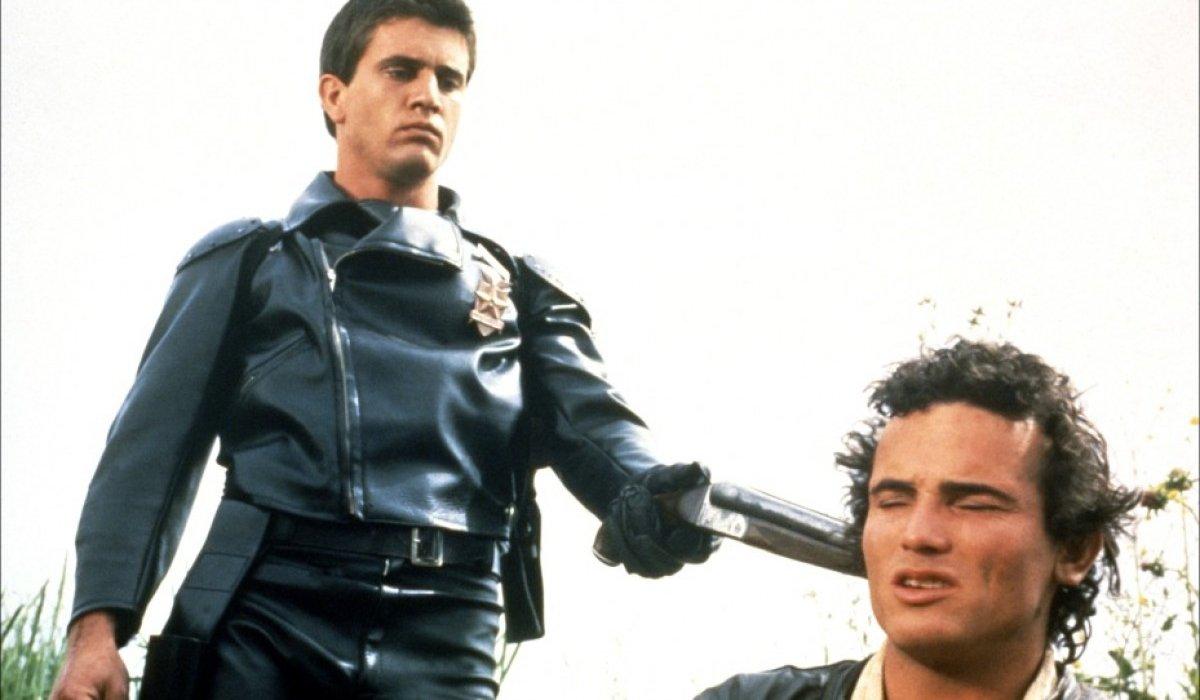 Max Max Mel Gibson holds a man at gunpoint