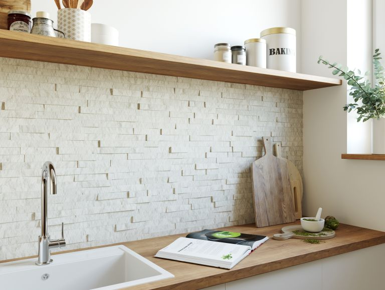 white neutral split mosaic tile backsplash in a white kitchen with wood countertops and natural wood cooking utensils