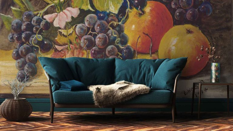blue sofa against wallpapered wall with large fruit motif