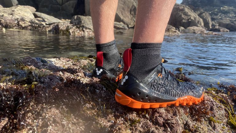 Best water shoes: person wearing Vivobarefoot tempest water shoes on a rock near the sea