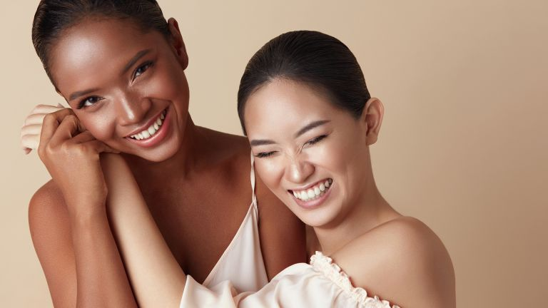 Diversity. Beauty Models Portrait. Cheerful Asian And Mixed Race Women Bonding Hands And Laughing. Different Ethnicity Female With Natural Makeup Standing Together Against Beige Background. - stock photo