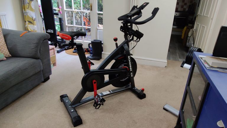 the subject of this review, the Schwinn 800IC exercise bike, placed in a busy room surrounded by home weights and furniture
