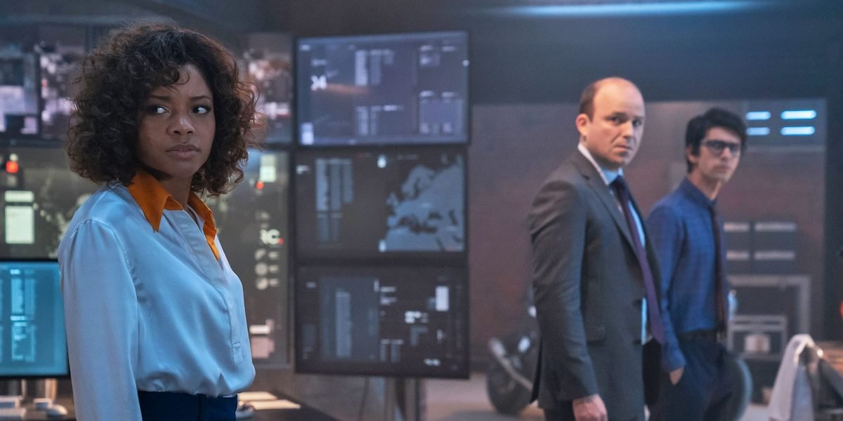 Ms. Moneypenny, Bill Tanner and Q stand in front of a bank of large monitors in 'No Time To Die'