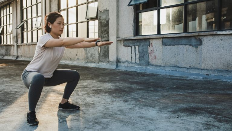 woman doing bodyweight exercises in empty room