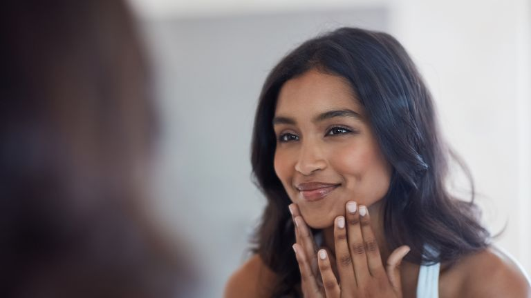 woman applying skincare in mirror