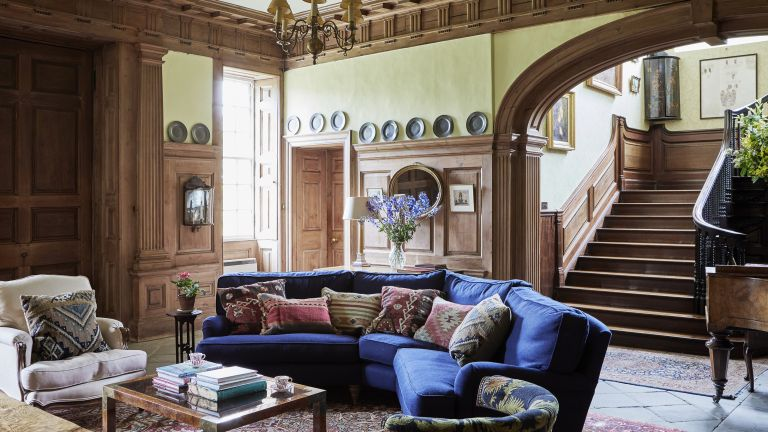 grand georgian panelled wood entrance hall with blue curved sofa and sweeping staircase