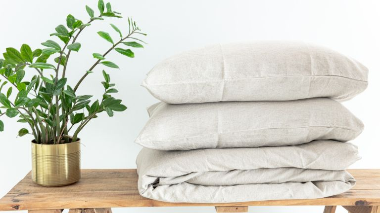 stack of bed linen on a table with a potted plant