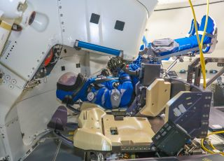 An anthropomorphic test device or flight dummy nicknamed Rosie the Rocketeer appears strapped into a seat in Boeing's Starliner capsule before the vehicle's second uncrewed flight test, scheduled to launch on July 30, 2021.
