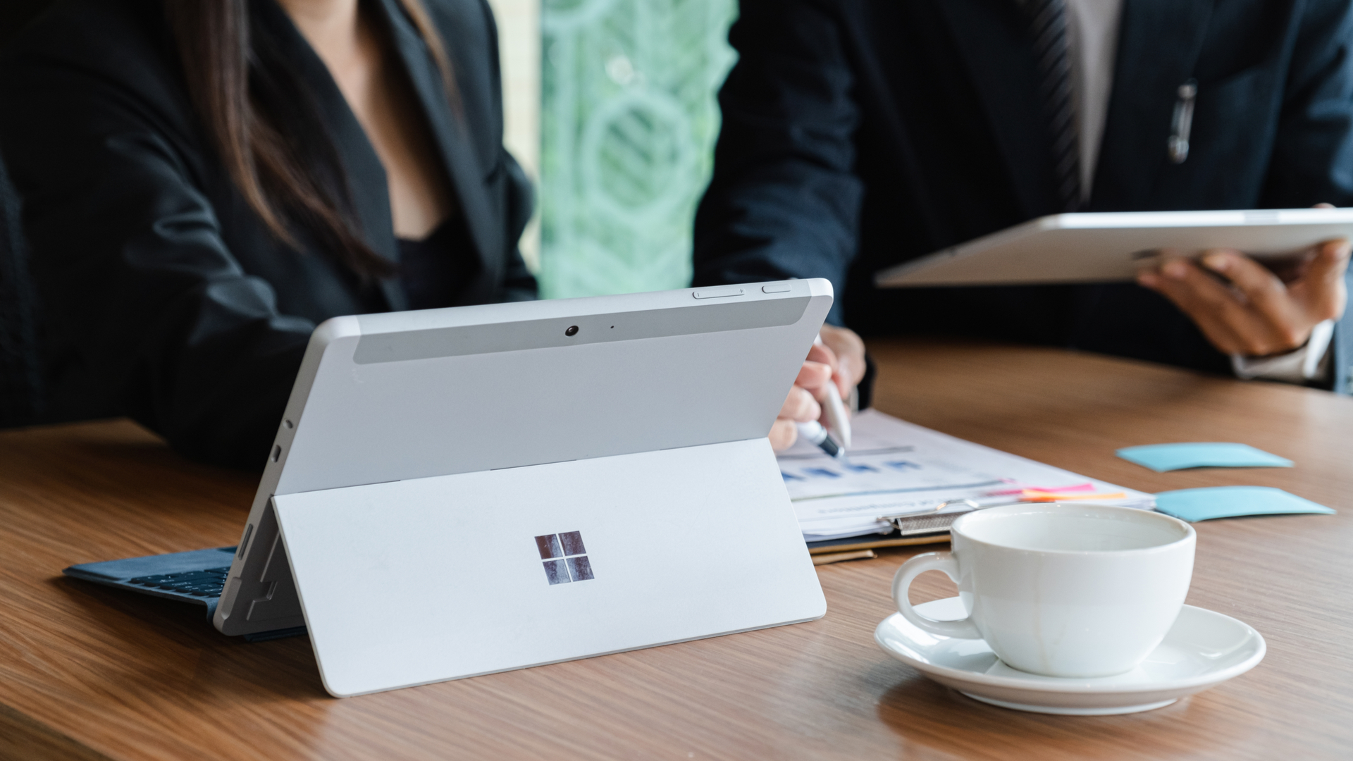 Microsoft Surface tablet on desk with businesman and businesswoman