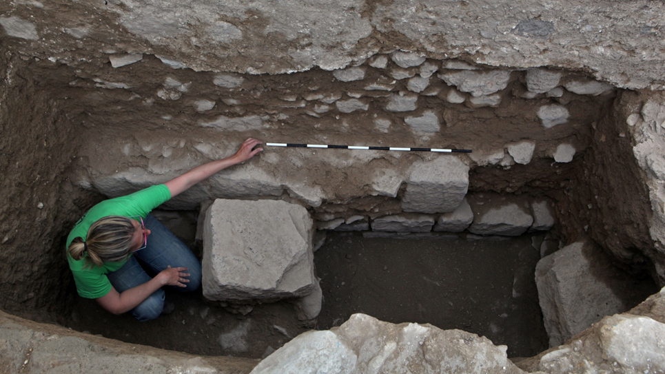 An archaeologist examines the foundation of the first mosque right above remains of a monumental Roman building.