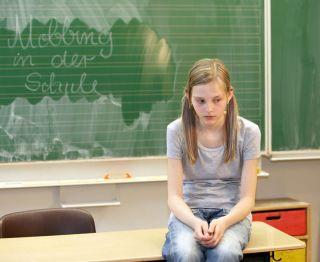 sad girl sits on school desk