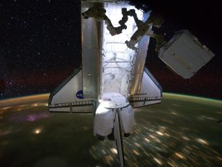 Backdropped by a night time view of the Earth and the starry sky, the Space Shuttle Endeavour is photographed docked at the International Space Station on May 28, 2011. The STS-134 astronauts left the station the next day on May 29, after delivering the A
