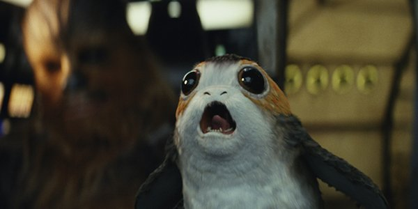 A Porg annoying Chewie while he's trying to drive.