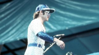 Pop singer Elton John performs onstage at Dodger Stadium in a blue and white sequined outfit Dodgers uniform on October 25, 1975 in Los Angeles, California