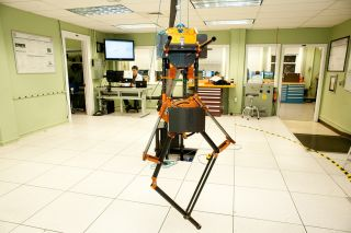 ATRIAS robot stands on two spindly legs in the middle of an engineering laboratory