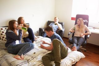 Teenagers sit around in someone's bedroom, drinking alcohol.