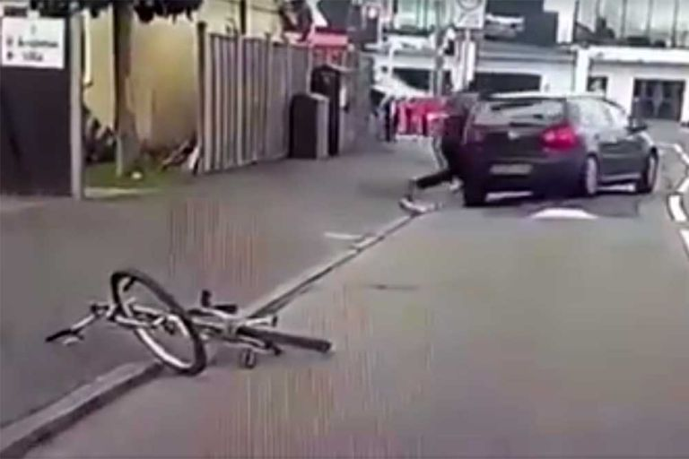 The rider of the bike gets up after being hit by the Volkswagen Golf and smashes the rear windscreen