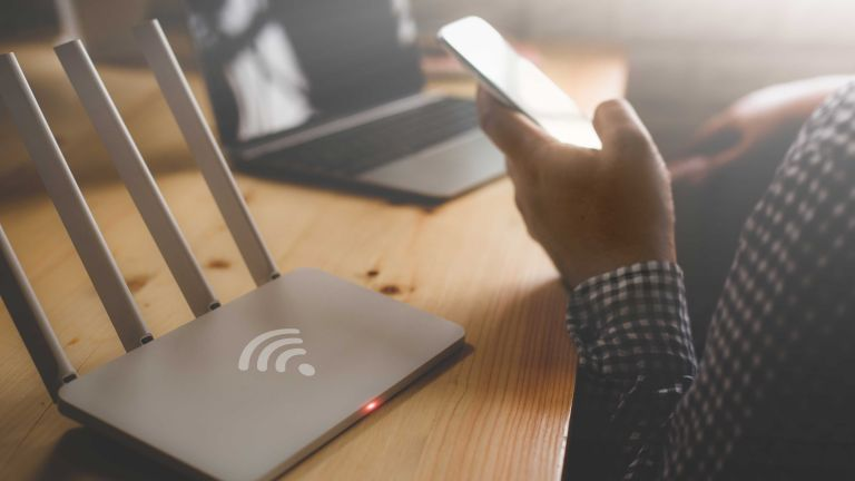 Best broadband deals: person on phone next to Wi-Fi box