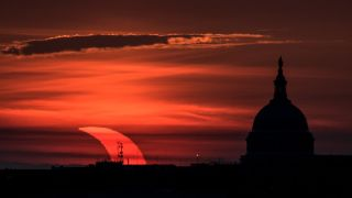 A partial solar eclipse seen at sunrise with the U.S. Capitol building on display in an image taken June 10, 2021, by NASA photographer Bill Ingalls.
