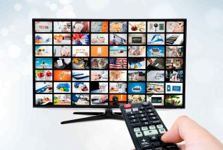 Widescreen ultra high definition TV screen with hand on remote