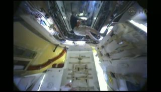 View inside SpaceX Dragon capsule at space station with cosmonaut Oleg Kononenko inside.