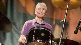 A photograph of Charlie Watts behind the drums
