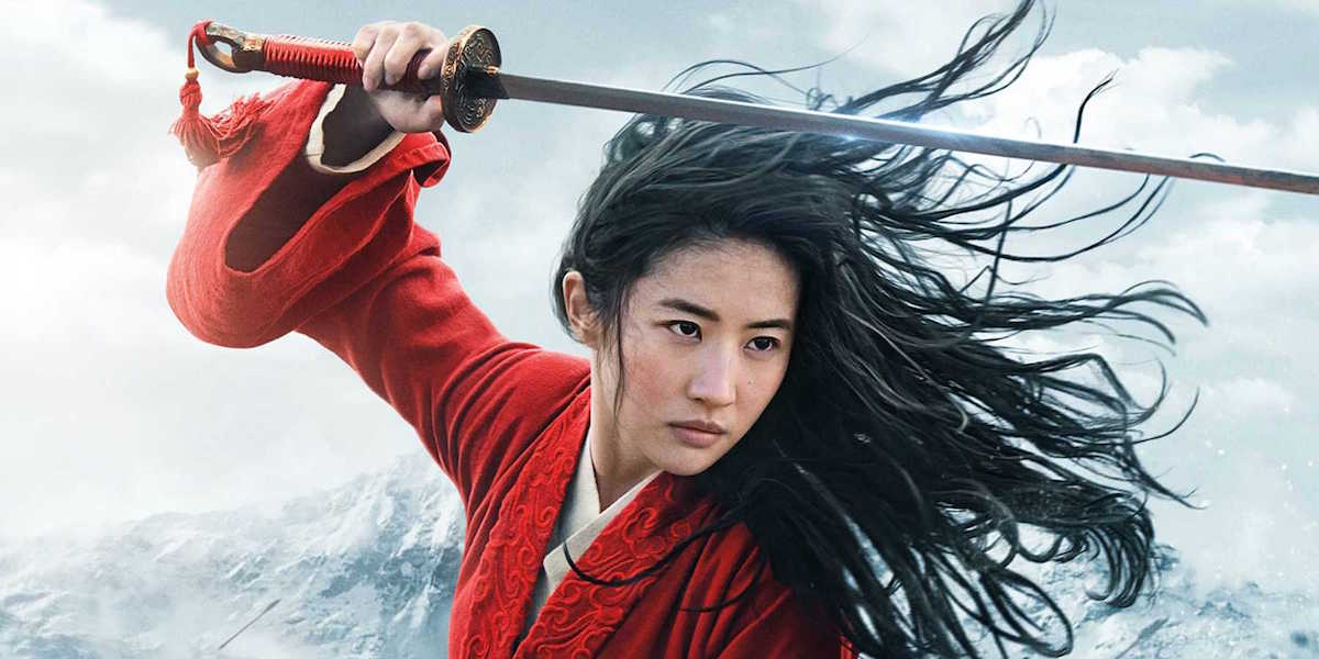 Mulan raises her sword above her head in a promotional picture from the 2020 live action adaptation.