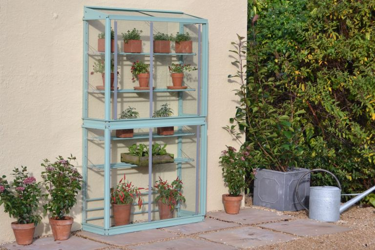 blue mini greenhouse in a garden with plant pots and a watering can