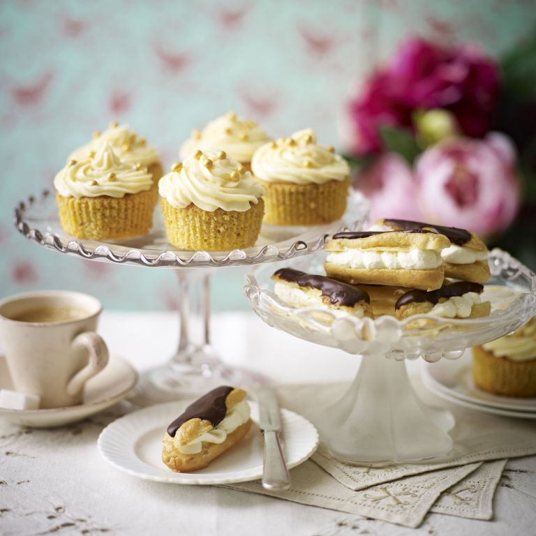 Chocolate and ginger cupcakes on a glass cake stand with eclairs and flowers
